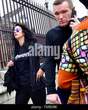 London, England, UK. Woman wearing reflective sunglasses and man on mobile phone, by the Houses of Parliament, Westminster - Stock Image