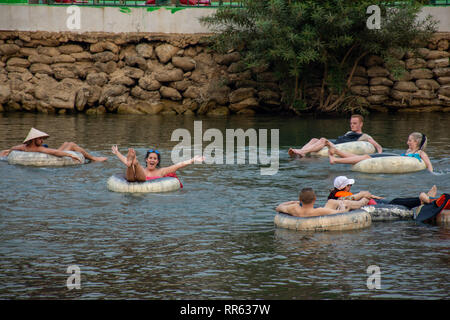Western tourist back packers enjoy floating and partying in ring tubing, Vang Vieng, Loas. - Stock Image