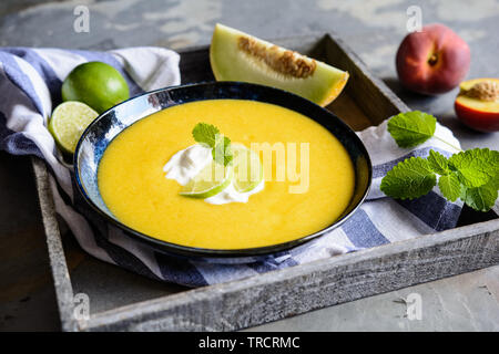 Refreshing  summer fruit soup with Galia melon and peaches - Stock Image