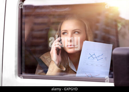 Serious business woman in the car going to work, analyzing graphics and discussing it on the phone - Stock Image