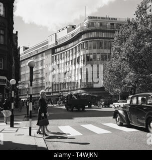 1960s, historical, two ladies walking across a level crossing at Sloane Square, London, with the department store, Peter Jones seen in the distance. - Stock Image