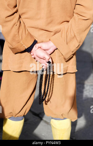 Rear view of Buddhist monk wearing short set clothing holding prayer beads or malas. - Stock Image