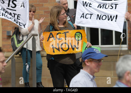 An Activists from the Climate Change group Extinction Rebellion holds a banner saying ÒAct NowÓ during a demo outside Derby City Council house on 22/05/2019 - Stock Image