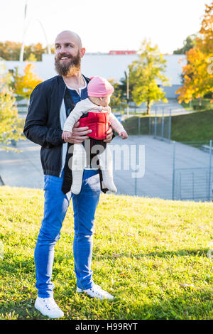 Father with baby girl in baby carrier standing in park - Stock Image