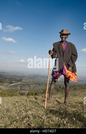 Vertical image of smiling Maasai elder standing on a hill with view of Kenya in background. Africa. - Stock Image