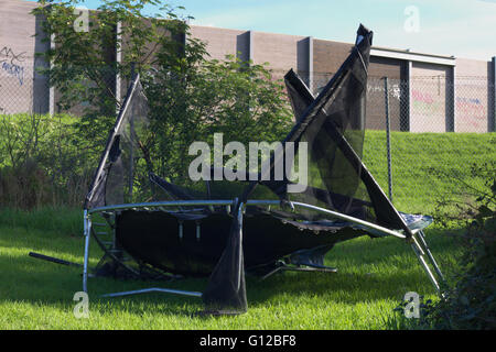 Storm damaged trampoline on green reserve alongside freeway barrier wall. - Stock Image