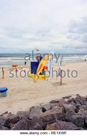 Kolobrzeg, Poland - August 10, 2018: Beach with guard tower showing red flag. It is a cloudy windy day with many waves. Out of safety swimming is forb - Stock Image