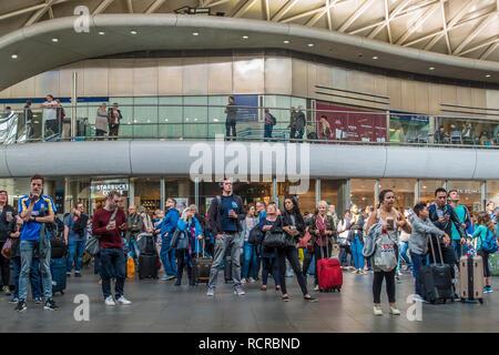 Rail Passengers,Watching,Departure Board,Kings Cross Station,Euston Road,London,England,UK - Stock Image