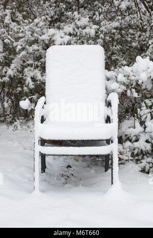 Two stacked garden chairs in snow - Stock Image