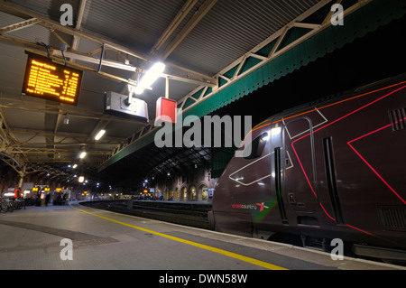 A Cross Country train at a passenger platform at Temple Meads Station on the Western region of the UK railway network at night. - Stock Image