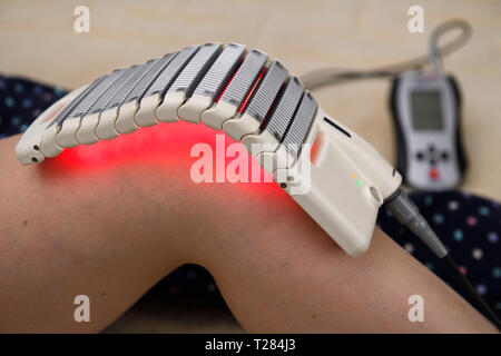 Cold laser LED array pad treatment for knee therapy and healing - Stock Image