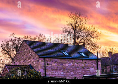 Beautiful early morning winter dawn sunrise, with a multi coloured sky above a barn conversion property. Langtoft, - Stock Image