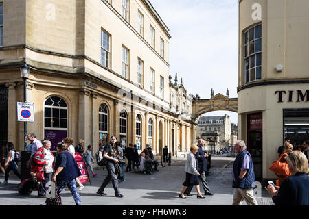 People and tourists walking along Stall street in the city of Bath with a view down York street with the bridge in the background - Stock Image