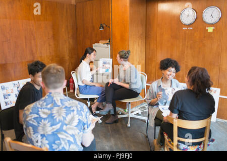 Creative designers discussing proofs in office - Stock Image