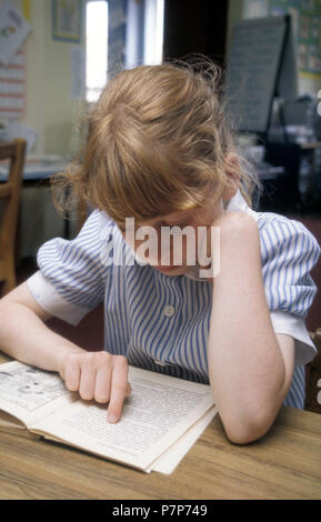 little girl reading in primary school - Stock Image
