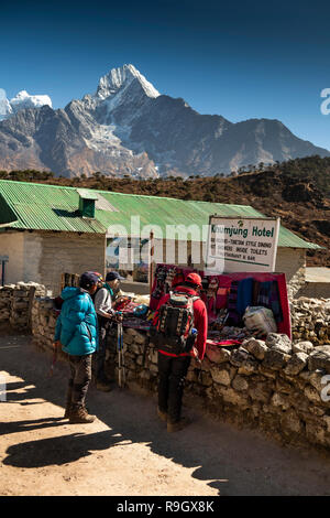 Nepal, Everest Base Camp Trek, Khumjung village, trekker and Sherpa guide at small tourist souvenir stall outside local guest house lodge - Stock Image