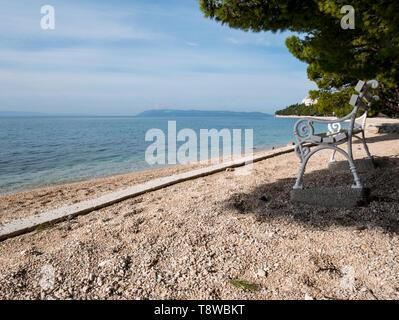 Wooden bench on empty beach close to the sea in Tucepi, Croatia - Stock Image