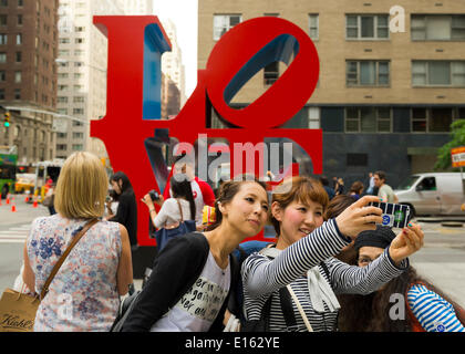 Manhattan, New York, U.S. - May 21, 2014 - Several girl friends take Selfies photos with a cell phone, with the colorful famous LOVE sculpture by Robert Indiana on 6th Avenue in the background, during a pleasant Spring day in Manhattan. - Stock Image