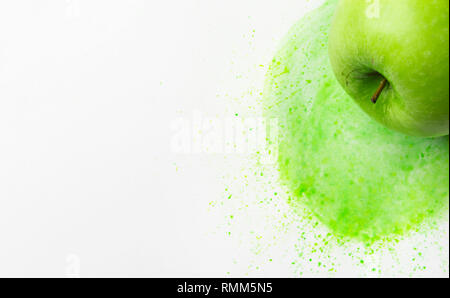 Green raw apple on hand drawn watercolor background of chartreuse yellow color mixture with splashes paintbrush strokes. Mixed media image combination - Stock Image