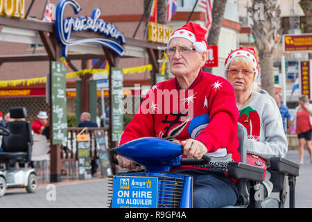 Benidorm, Costa Blanca, Spain, 25th December 2018. British tourists dress for the occasion on Christmas Day in this favourite getaway destination for Brits escaping the cold weather at home. Temperatures will be in the mid to high 20's Celsius today in this mediterranean hotspot. Middle aged couple wearing Christmas Jumpers driving a mobility scooter outside on the sea front promenade on Levante Beach. - Stock Image