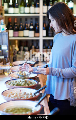 Female Customer In Delicatessen Filling Pot With Green Olives - Stock Image