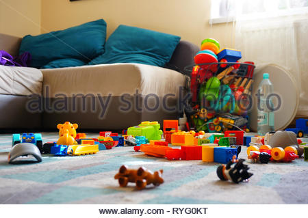 Poznan, Poland - March 2, 2019: Mix of Lego Duplo blocks laying around on a carpet floor in a living room with sofa. - Stock Image
