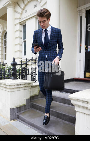 Young man in checked suit looking at phone, leaving building - Stock Image