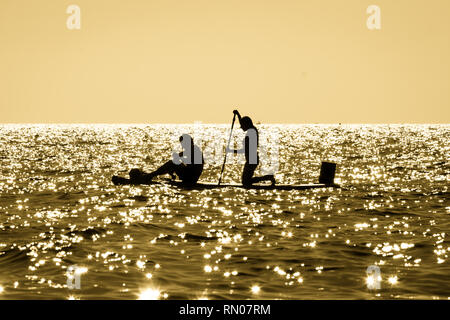 Picture of a Silhouette of a young couple paddling on a surf at sunset in Maro, Andalusia, Spain. - Stock Image