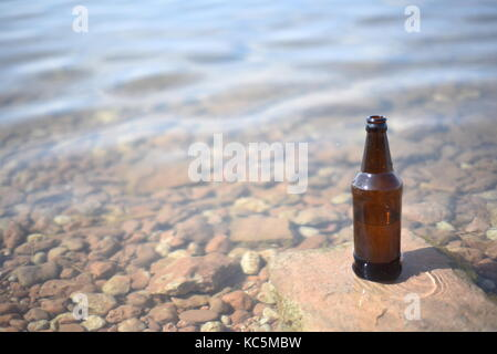 Single brown glass bottle with a rippling water background and natural sunlight - Stock Image