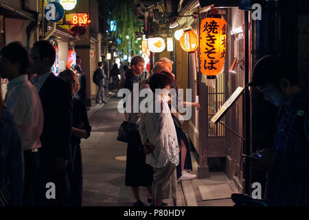 Pedestrians looking at restaurant and shop windows in pedestrianised Kyoto street at night near Kiya-Machi street, in Japan. - Stock Image