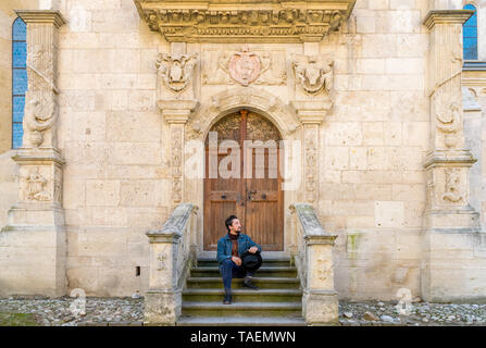 Portrait of a young man sitting against a beautiful old medieval cathedral door. A man in front of a an old architecture church entrance door in Alba  - Stock Image