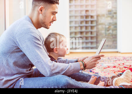 father and toddler son sit on floor at home using tablet - Stock Image