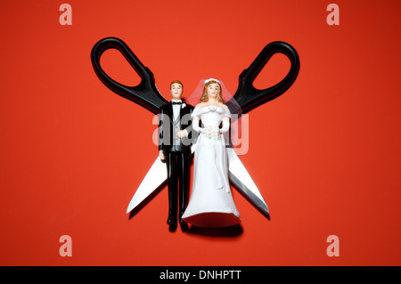 Plastic miniature wedding figures with scissors on a red background. - Stock Image
