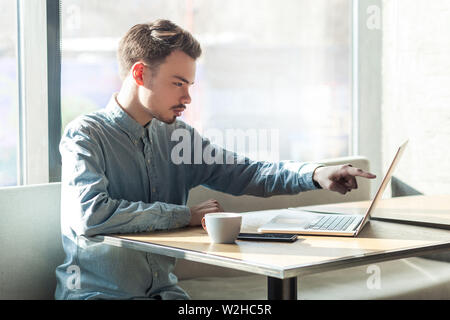 Side view portrait of serious young businessman in blue shirt are sitting and pointing at target on laptop dislpay with attention and serious face. in - Stock Image