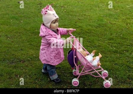 toddler girl pushing dolly in toy pram outside - Stock Image