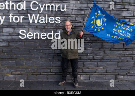 Cardiff, Wales, UK. 10th March 2019. Edmund Sides sets off from the Senedd building in Cardiff Bay on the Cardiff - Newport leg of his walk. He is walking from Swansea to London to join the People's Vote march on 23rd March.   Setting off from Swansea on Wednesday 6th March, Ed aims to arrive in London on 22nd March, in time to join other Swansea for Europe campaigners who will be flying the flag for Swansea at the People's Vote march.  The last march, in October, was one of the biggest in British history, drawing 700,000 people. Credit: Polly Thomas/Alamy Live News - Stock Image
