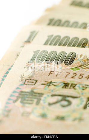 Close up of a pile of 10000 yen notes on white background. - Stock Image
