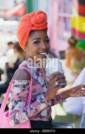 Smiling young woman in headscarf drinking smoothie - Stock Image
