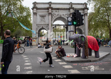 London, England, UK - April 23, 2019: Cyclists and pedestrians travel through a protest camp by Extinction Rebellion at Marble Arch in central London. - Stock Image