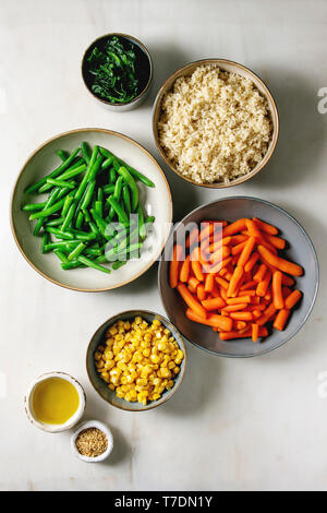 Couscous with parboiled vegetables baby carrots, green beans, sweet corn, spinach in separate ceramic plates with sesame seeds and olive oil. Vegan fo - Stock Image