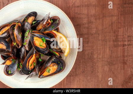 Marinara mussels, moules mariniere, close-up overhead shot on a dark rustic wooden background with copy space - Stock Image
