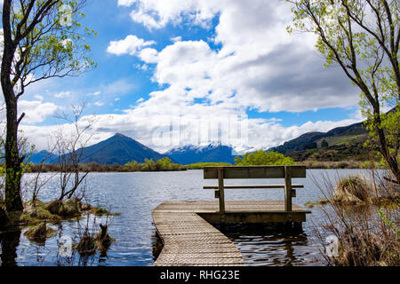 Bench at the end of a boardwalk by a lake - Stock Image