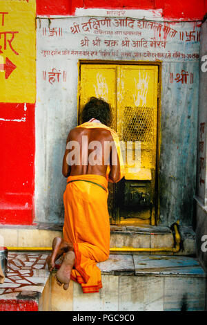 A Man parays in front of the door of a temple in Varanasi, India - Stock Image