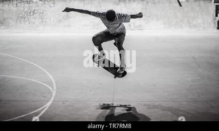 A skateboarder preforming a trick in a skatepark - Stock Image