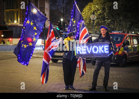 Westminster, London, UK, 20th Mar 2019. Anti-Brexit protesters don a 'revoke' sign with neon letters inviting PM Theresa May to revoke Article 50. Credit: Imageplotter/Alamy Live News - Stock Image