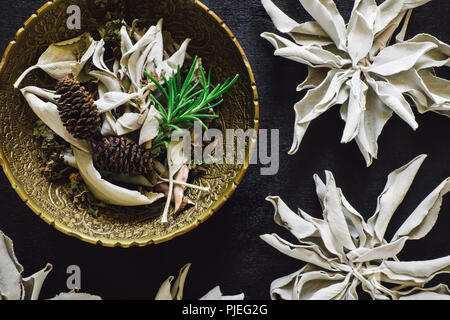 Bowl of Mixed Herbs and White Sage on Black Wood - Stock Image