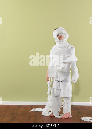 Boy 4-7 wrapped in toilet paper - Stock Image