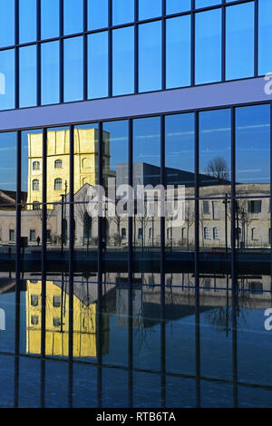The Fondazione Prada buildings are reflected in a glass building of the recently finished piazza Adriano Olivetti,in the new Symbiosis district, Milan - Stock Image