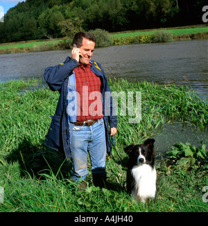 A British farmer with his dog standing by a river field talking on mobile phone in Carmarthenshire Wales UK  KATHY DEWITT - Stock Image