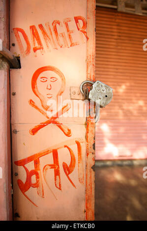 DANGER and skull and crossbones painted on an electricity cupboard. In Hindi also. India - Stock Image